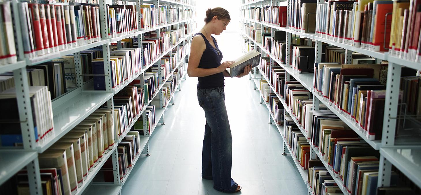 étudiante qui consulte dans les rayons de la bibliothèque